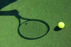 Skugga av ett tennisracket i hand med en boll Arkivfoton