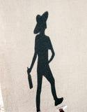 Skugga av flickan i hatt med flaskan som går på solig dag royaltyfri bild