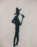 Skugga av flickan i hatt med flaskan som går på solig dag royaltyfri fotografi