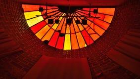 Skugga av ljusa instalation- och målat glassfönster i vibrerande röda färger Royaltyfri Fotografi