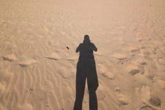 Skugga av mannen på stranden som tar fotoet Royaltyfri Fotografi