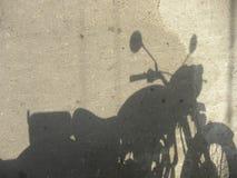 Skugga av mopeden som parkeras på vägen arkivfoton