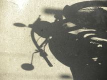 Skugga av motorcykeln som parkeras på vägen arkivbild