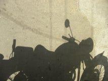 Skugga av motorcykeln som parkeras på vägen royaltyfria bilder