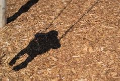 Skugga av pysen på gunga på parkerar på komposttäckning Royaltyfri Foto