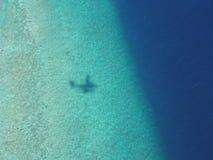 Skugga av sjöflygplanet på barriär för korallrev av atollen i Maldiverna fotografering för bildbyråer