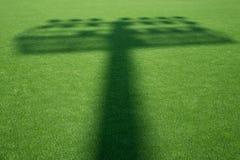 Skugga av stadionljus på gräset Royaltyfri Bild