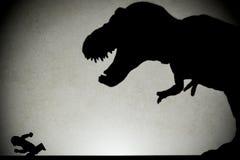 Skugga av tyrannosarien som jagar människan på väggen arkivbild