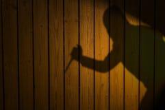 Skugga eller kontur av brottslingen med kniven på staketet royaltyfria bilder