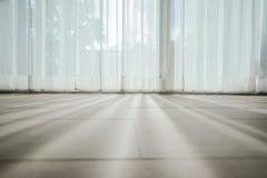 Skugga från att skina till och med ett fönster och gardinerna arkivbilder