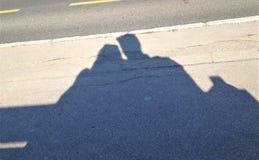 Skugga på den gråa betongen av två personer som sitter på en bänk fotografering för bildbyråer
