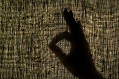 Skuggahanden visar gesten väl, som en gest på ett slitet royaltyfria foton