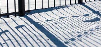 Skuggamodell av metallstakettextur på snö Royaltyfri Foto
