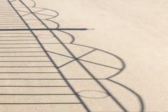 Skuggan av detbearbetade staketet på asfalt fotografering för bildbyråer