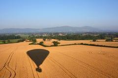 Skuggan av en ballong för varm luft som flyger över lantlig jordbruksmark Fotografering för Bildbyråer