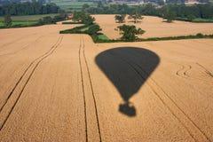 Skuggan av en ballong för varm luft som flyger över lantlig jordbruksmark Royaltyfri Foto