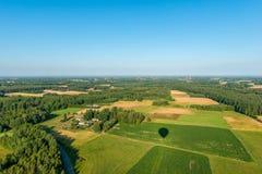 Skuggan av en ballong som flyger över kultiverade fält med en sikt av den molnfria himlen arkivfoto