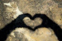 Skuggan av en hjärta reflekterade på en sten Arkivbilder
