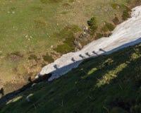 Skuggan av fotvandrarna i snön som klättrar till överkanten Arkivfoto