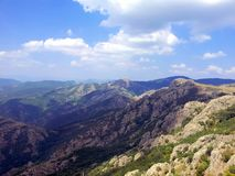 Skuggan av molnet är på vaggar i bergen av Bulgarien mot den blåa himlen med vita moln Arkivbild