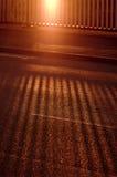Skuggan av staketet på den tomma asfaltvägen, bro på solnedgången Arkivbilder