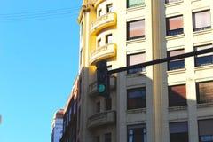Skuggig grön trafikljus med blå himmel arkivbild