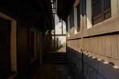 Skuggig sten-stenlagd gränd i kinesiska traditionella hus på soligt D Arkivfoton