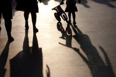 Skuggor av en familj med lilla flickan som skjuter en cykel arkivbild