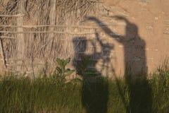 Skuggor av en man och en kvinna mot en vägg royaltyfri foto