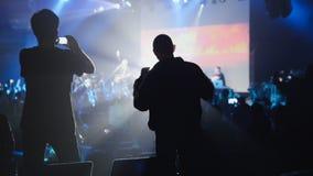 Skuggor av folk som gör en video av konserten på en mobiltelefon royaltyfri foto
