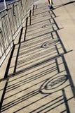 Skuggor av staketet på betongen, noterar grunt djup av fältet gå mannen med ingen framsida Arkivbilder