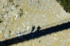 Skuggor av två personer på den torra flodsängen under en upphängningbrud Fotografering för Bildbyråer