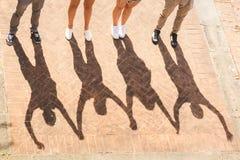Skuggor av vänner som tillsammans rymmer och lyfter händer Royaltyfri Fotografi
