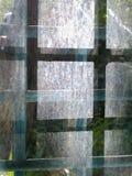 Skuggor på exponeringsglaset av ett gallerförsett fönster arkivfoto