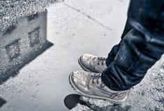 Skuggor skor, jeans som vindsurfar i vattnet Arkivbilder