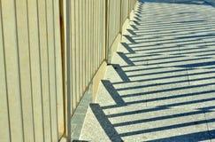 Skuggor spelar mellan räcket och trappa i staden Arkivbild