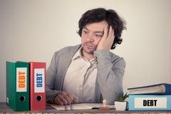 Skuldtext på limbindningarna, bekymrad bussinesman som tänker vid arbetsskrivbordet arkivfoton
