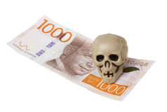 Skull on banknote. One small plastic skull on a Swedish 1000 banknote isolated on white Stock Photos