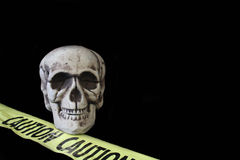Skull on Black. Skeleton on black background with yellow caution tape. Copy space royalty free stock images