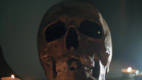 Skull with black eyes covered in white smoke. The hand places the candles around the human skull. Halloween stock footage
