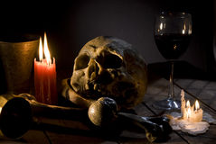Skull and bones. Real skull and bones over a table, with candles and chalice stock photography