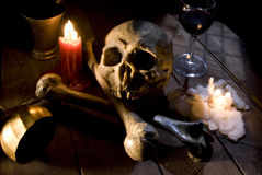 Skull and bones. Real skull and bones over a table, with candles and chalice royalty free stock photos