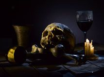 Skull and bones. Real skull and bones over a table, with candles and chalice stock photos