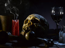 Skull and bones. Real skull and bones over a table, with candles and chalice Royalty Free Stock Photo
