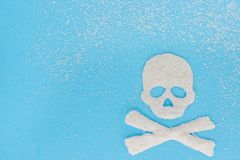 Skull bones made from sugar and scattering of granulated sugar,. Skull bones from sugar and scattering granulated sugar, blue background. Copy space, Concept stock photos
