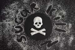 Skull bones made from sugar and scattering of granulated sugar,. Text SUGAR KILL, Skull bones from sugar and scattering granulated sugar, black background. Top royalty free stock images