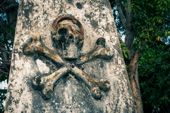 Skull and bones. Photo of stone column with symbol of death, skull and bones in cemetery in Surabaya in Java province, Indonesia stock photos