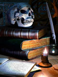 Skull and books. An old fashioned table with a candle, with ancient books and a skull over them stock illustration