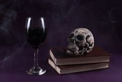 Skull on books and wine glass on purple dark and smoked background stock photo