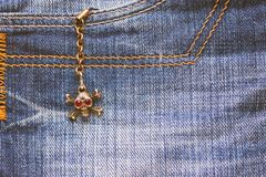 Skull brooch on torn jeans . Royalty Free Stock Photo